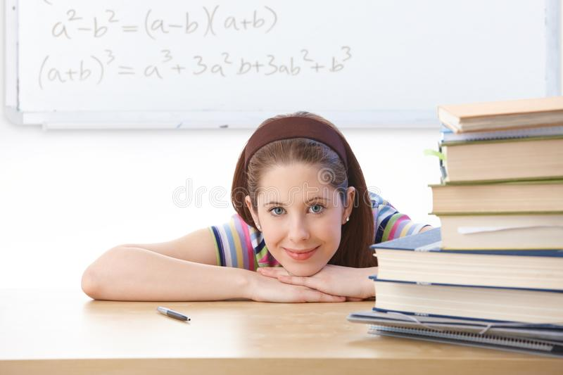 Teenage girl in classroom smiling. Teenage girl sitting at desk in classroom front of whiteboard, smiling at camera royalty free stock photography