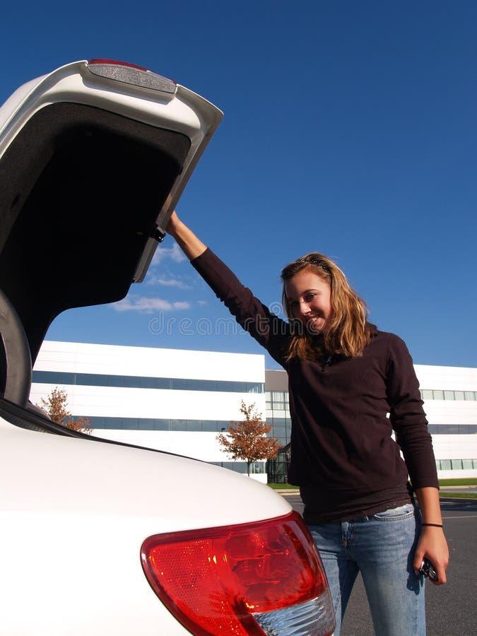 Teenage girl closing car trunk stock photos