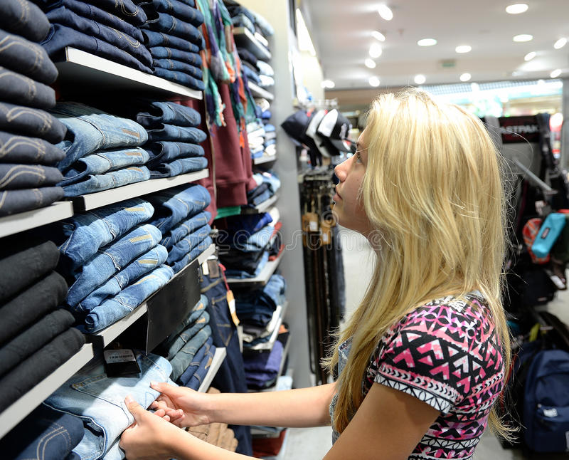 Teenage girl clothes shopping. Teenage girl looking at shelves of blue jeans in a clothing store royalty free stock images