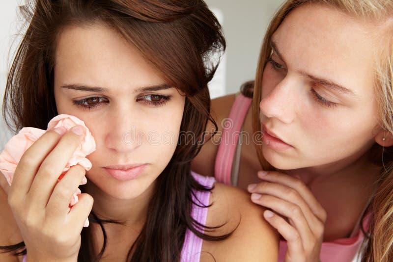 Teenage girl comforting tearful friend stock photos