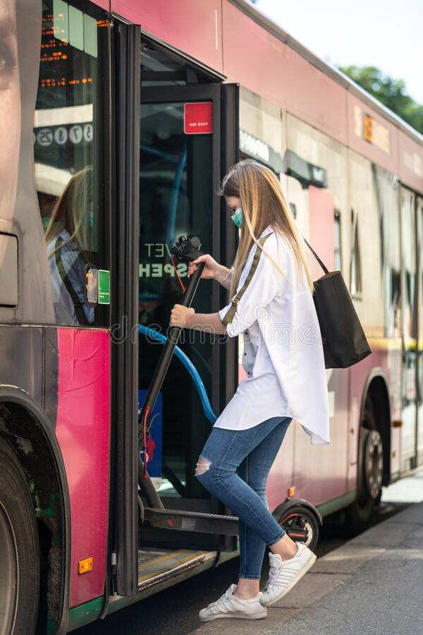 Teenage girl commuter entering city bus carring foldable electric urban scooter, wearing protective face mask against royalty free stock photos
