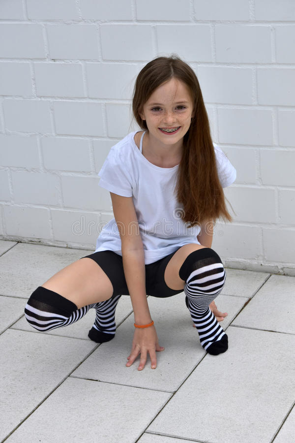 Teenage girl crouching. Friendly teenage girl with striped over knee stockings crouching on the ground stock photos