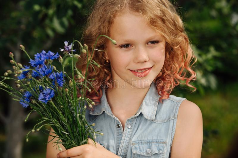 Teenage girl with curly hair is holding blue bouquet of meadow flowers stock images