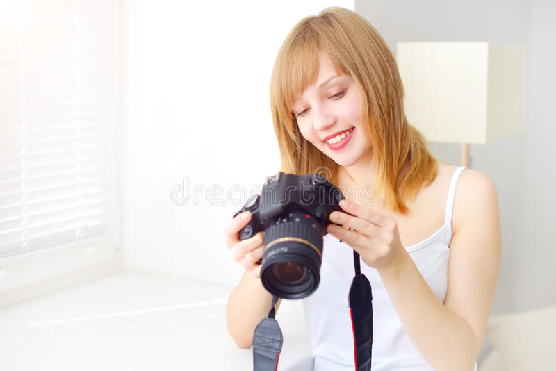 Teenage girl with digital camera. On light background royalty free stock photo