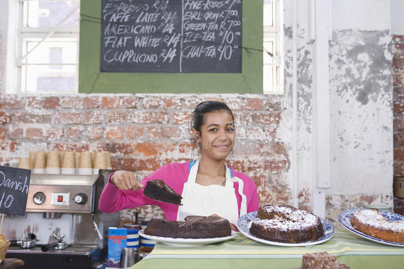 Teenage Girl Displaying Pastry In Shop royalty free stock photography