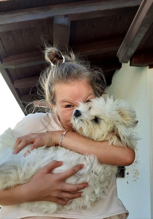 A teenage girl doing a face snd hidding behind a dog royalty free stock photos