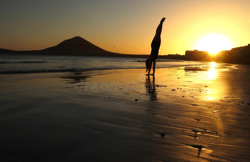 Girl doing handstand on beach at sunset in Tenerife, Spain royalty free stock images