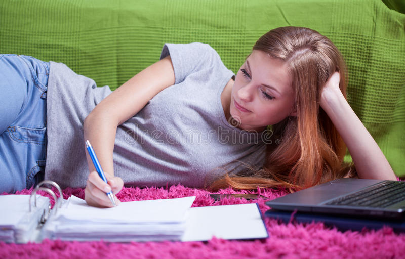 Teenage girl doing homework stock photos