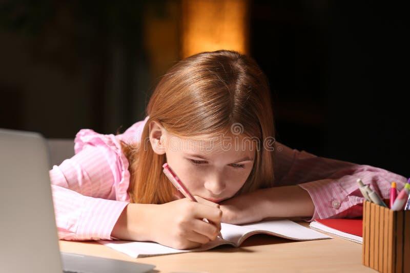Teenage girl doing homework at table royalty free stock photos