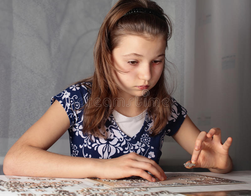 Teenage girl doing puzzle royalty free stock photography