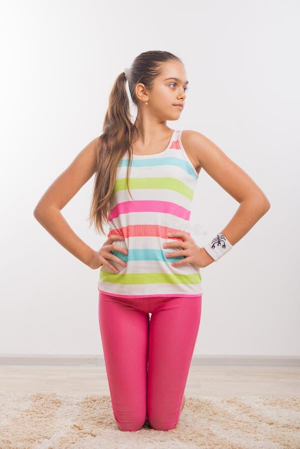 Teenage girl doing stretching exercises stock image