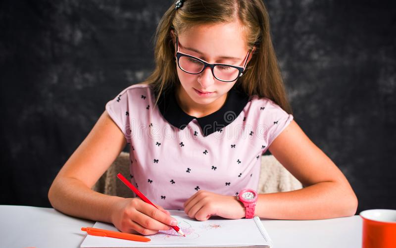 Teenage girl drawing with colorful pencils. Teenage girl drawing a flower with colorful pencils teenager brunette young coloring face sitting table cute home stock photos