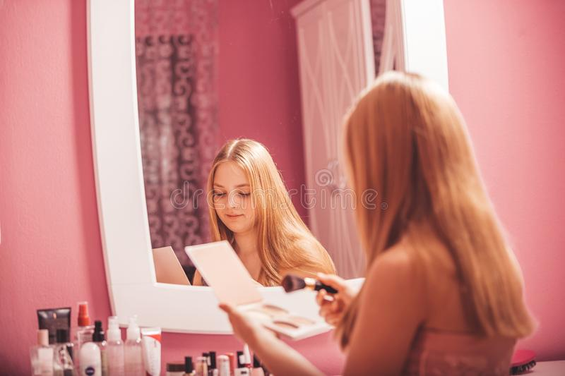 Teenage girl in a dress applying makeup on face at home stock photos
