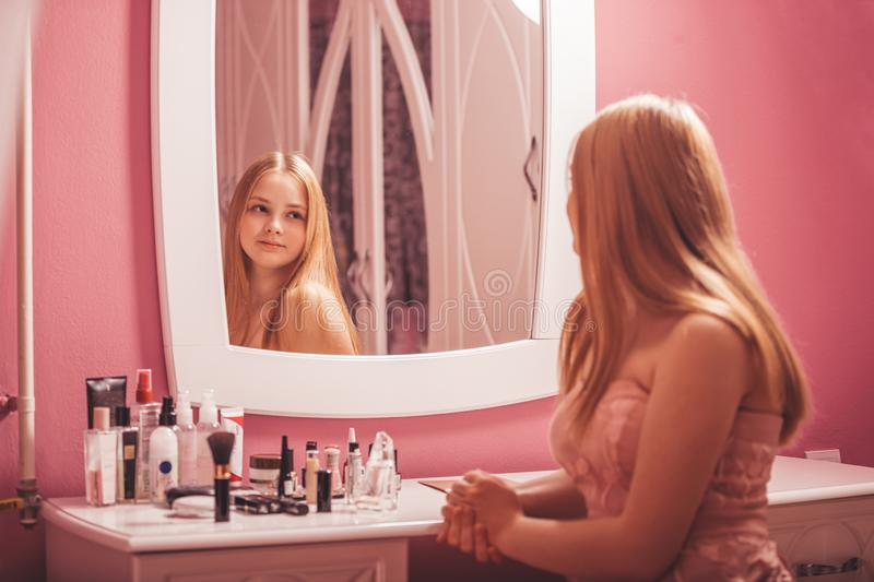 Teenage girl in a dress looking in the mirror and applying makeup stock photos