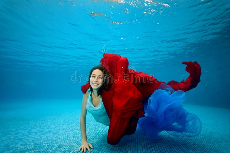 The teenage girl in the dress swims underwater at the bottom of the pool, plays with a red and blue cloth, looks at the camera royalty free stock images