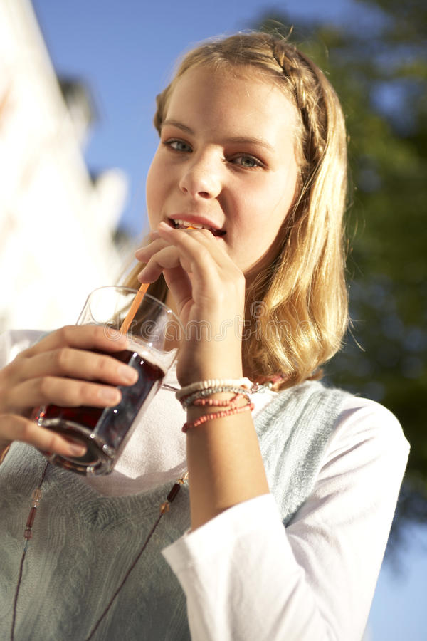 A teenage girl drinking. stock image
