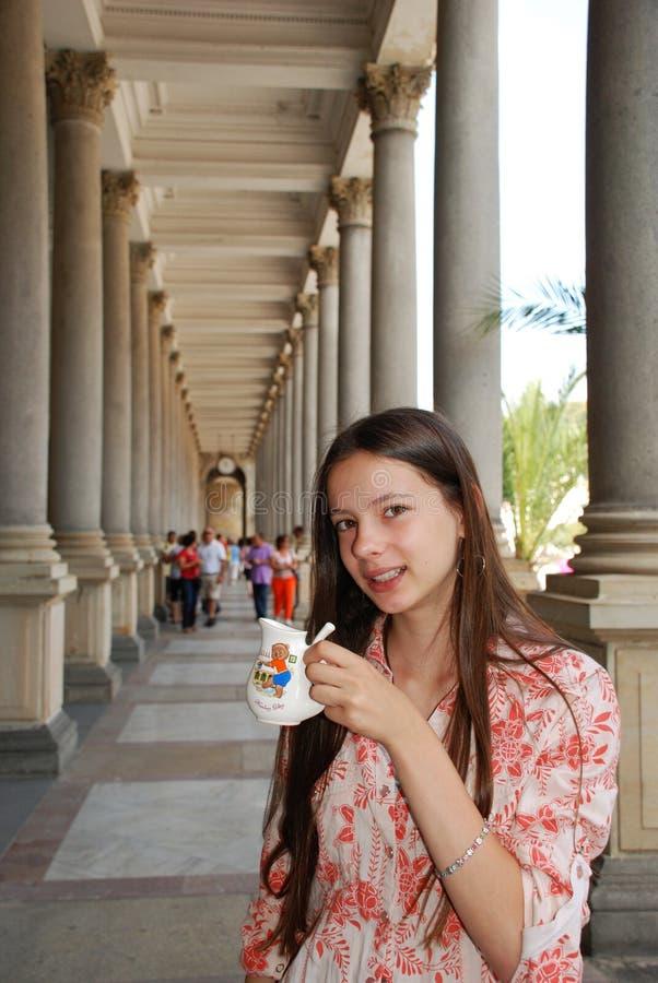 Teenage girl drinking mineral water. Beautiful teenage girl drinking mineral water in the Mill Colonnade. Karlovy Vary (Karlsbad, Carlsbad), Czech Republic royalty free stock photos