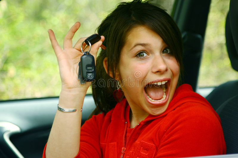 Teenage girl driver. A very happy teenage girl showing car keys, ready to drive a car stock image