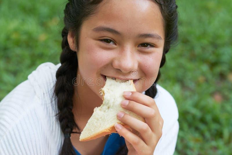 Teenage girl eating sandwich stock photo