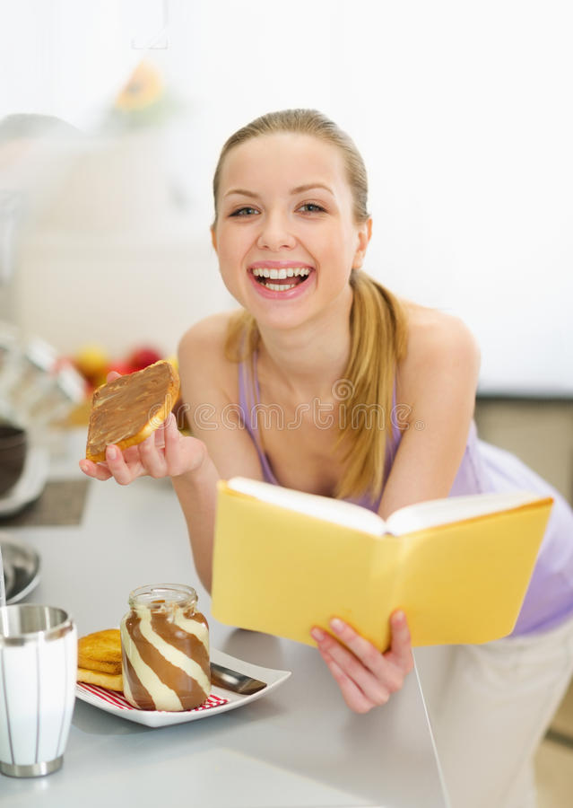 Teenage girl eating toast with chocolate cream. Happy teenage girl eating toast with chocolate cream while reading book royalty free stock photos