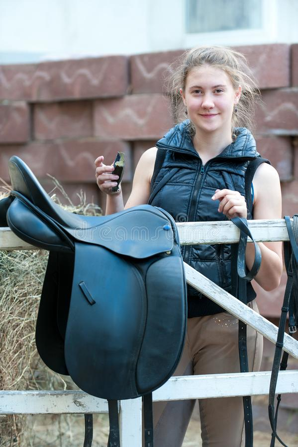 Teenage girl equestrian cleans black Leather Horse Saddle. Pretty teenage girl equestrian cleans black Leather Horse Saddle and equipment at farm looking in to stock images