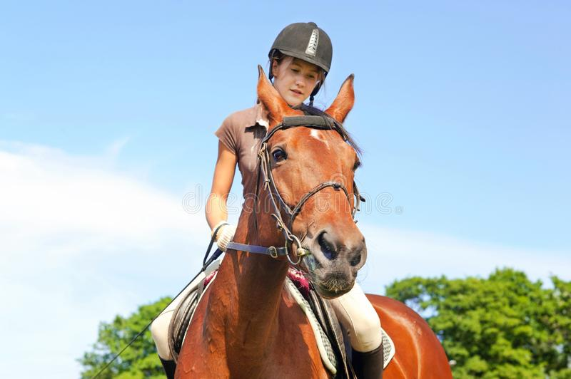 Teenage girl equestrian riding horseback. Vibrant summertime out stock photos