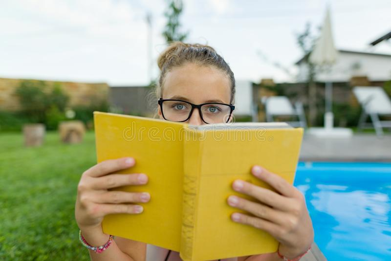 Teenage girl in glasses reads a book, background swimming pool, lawn near the house. School, education, knowledge, adolescents.  royalty free stock image