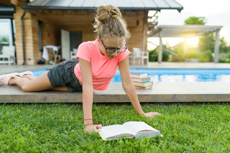 Teenage girl in glasses reads a book, background swimming pool, lawn near the house. School, education, knowledge, adolescents.  royalty free stock photo