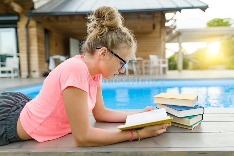 Teenage girl in glasses reads a book, background swimming pool, lawn near the house. School, education, knowledge, adolescents.  royalty free stock photos