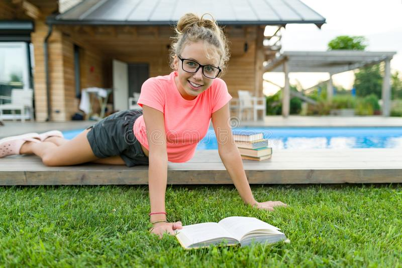 Teenage girl in glasses reads a book, background swimming pool, lawn near the house. School, education, knowledge, adolescents. Teenage girl in glasses reads a royalty free stock photo
