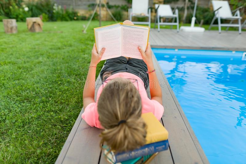 Teenage girl in glasses reads a book, background swimming pool, lawn near the house. School, education, knowledge, adolescents. Teenage girl in glasses reads a stock photography