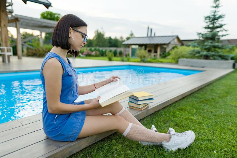 Teenage girl in glasses reads a book, background swimming pool, lawn near the house. School, education, knowledge, adolescents. Teenage girl in glasses reads a stock photo