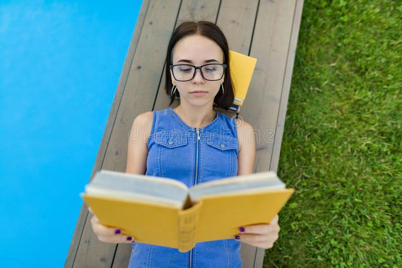 Teenage girl in glasses reads a book, background swimming pool, lawn near the house. School, education, knowledge, adolescents. Teenage girl in glasses reads a royalty free stock photos