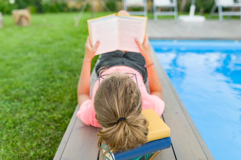 Teenage girl in glasses reads a book, background swimming pool, lawn near the house. School, education, knowledge, adolescents royalty free stock photography