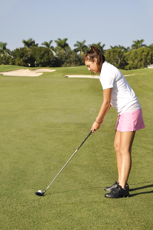 Teenage girl golfing royalty free stock image