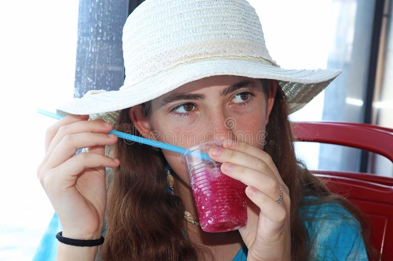 A teenage girl with a hat drinks a red cold drink stock images