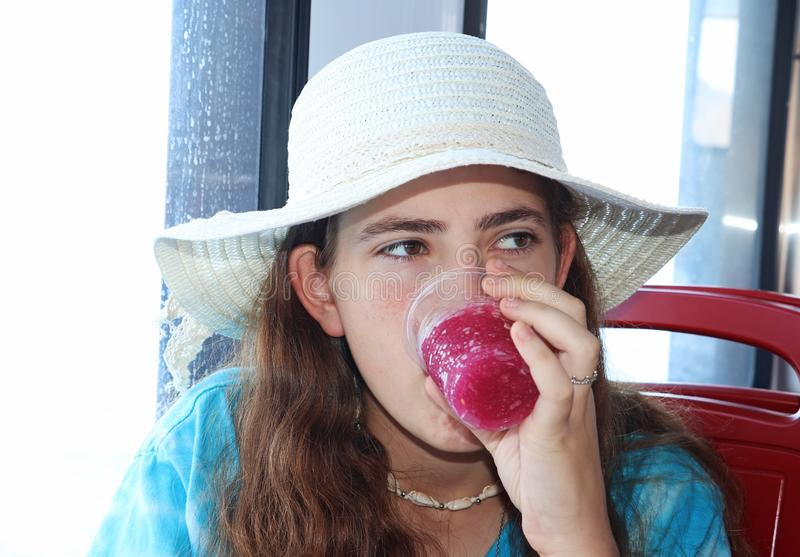 A teenage girl with a hat drinks a red cold drink stock image