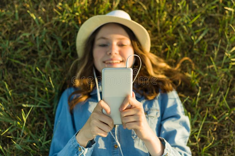 Teenage girl in hat with headphones lies on the green grass and looks into the phone. Focus on smartphone, top view. royalty free stock images