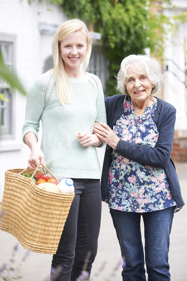 Teenage Girl Helping Senior Woman To Carry Shopping royalty free stock photography
