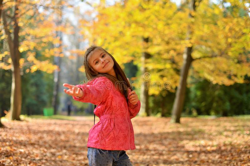 A teenage girl with her hair down walks in the forest Park in the autumn. stock photos