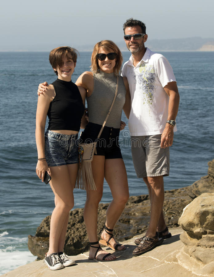 Teenage girl and her middle-aged parents standing by the ocean stock images