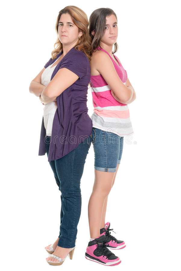 Teenage girl and her mother angry at each other. Standing back to back isolated on white stock images