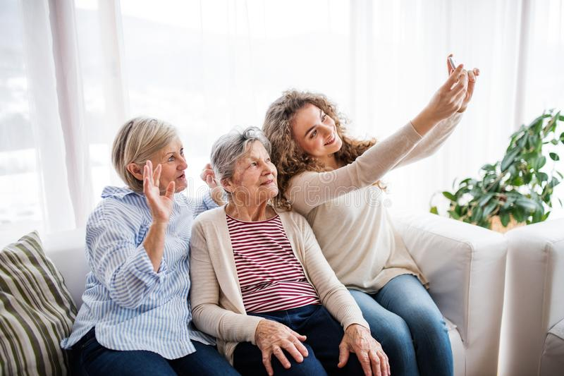 A teenage girl, mother and grandmother with smartphone at home. stock photography