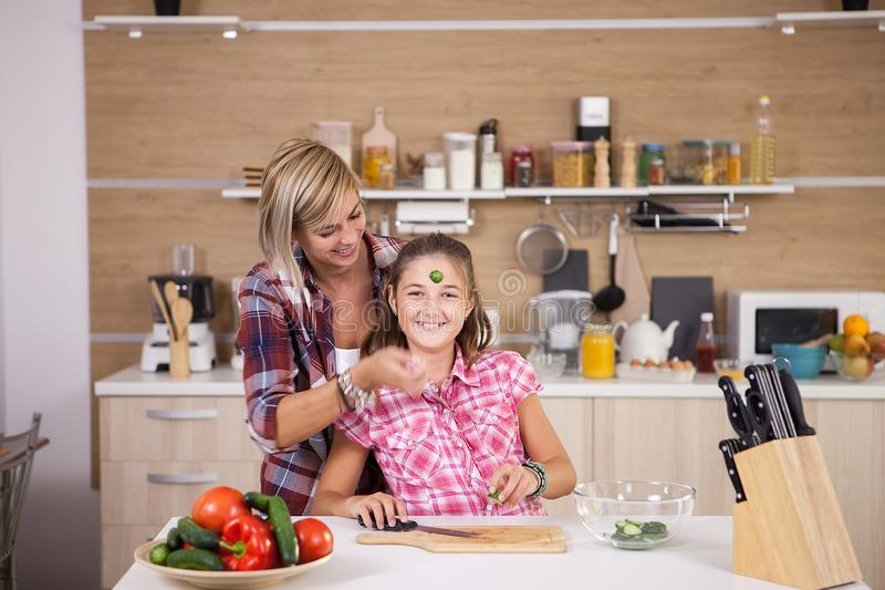 Teenage girl and her mother making healthy food for dinner. Happy family stock image