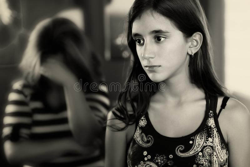 Teenage girl and her sad mother crying on the background. Teenage girl and her sad and worried mother crying on the background royalty free stock image