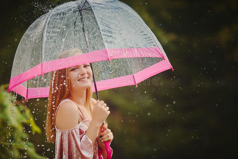 A teenage girl hid from the rain under an umbrella while walking through the park. She laughs and smiles, rejoices in the warm and. A teenage girl hid from the royalty free stock image