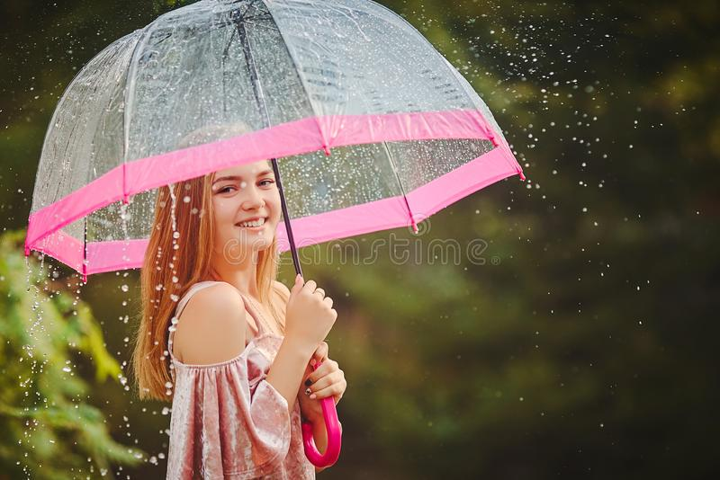 A teenage girl hid from the rain under an umbrella while walking through the park. She laughs and smiles, rejoices in the warm and. A teenage girl hid from the royalty free stock photos