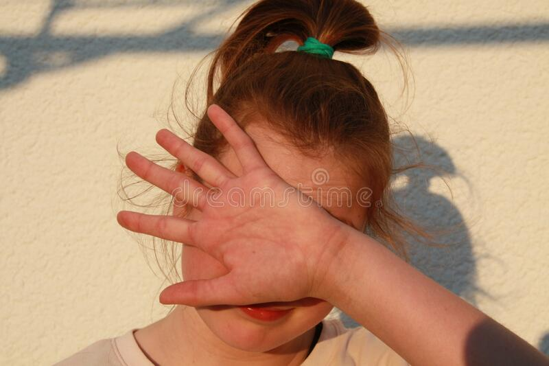 Teenage girl hiding her face with her hand stock photo