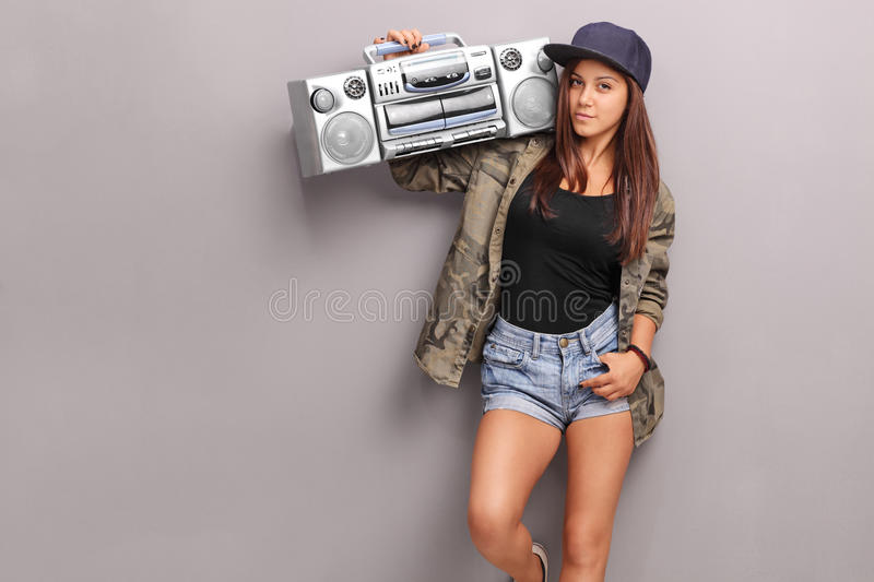 Teenage girl in hip hop clothes holding a ghetto blaster. Over her shoulder and looking at the camera royalty free stock images