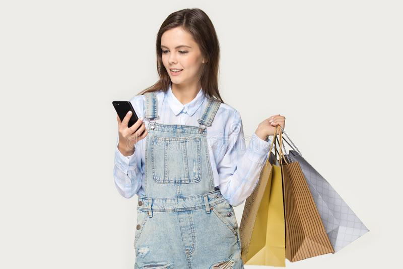 Teenage girl hold shopping bags buying online using smartphone royalty free stock photo